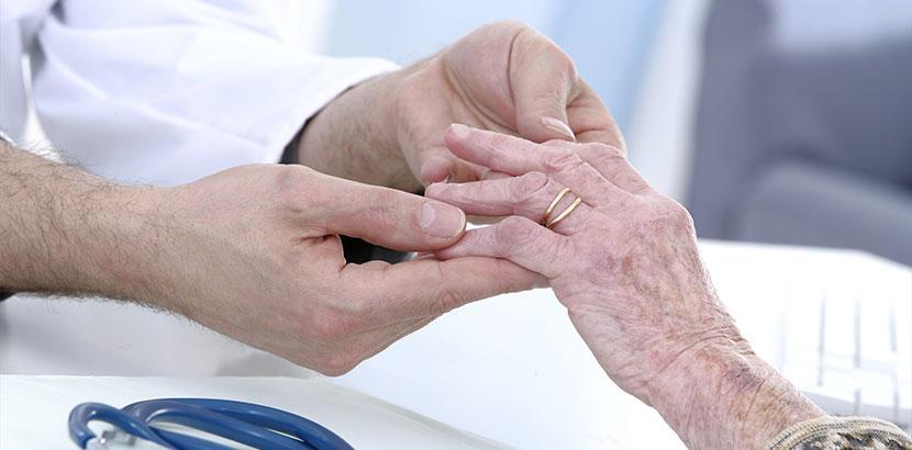 Handchirurg, der die Finger einer älteren Dame mit Arthrose untersucht.