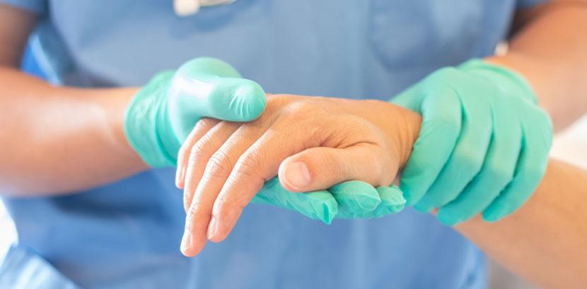Operateur, der die Hand eines Patienten hält. Handchirurg Wien.