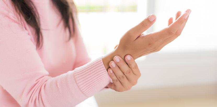 Junge Frau in einem rosa Pullover, die sich ihr schmerzendes Handgelenk hält. Handchirurg Wien.