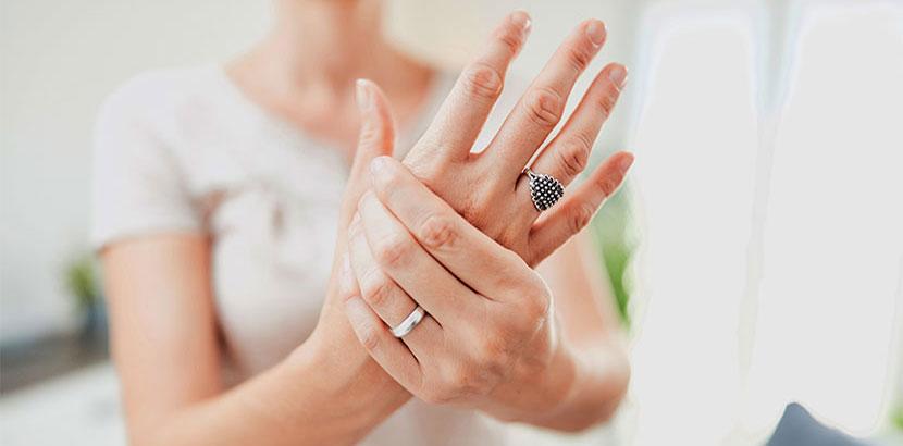 Junge Frau, die ihre schmerzende Hand in die Kamera hält und nach einem Handchirurgen sucht.