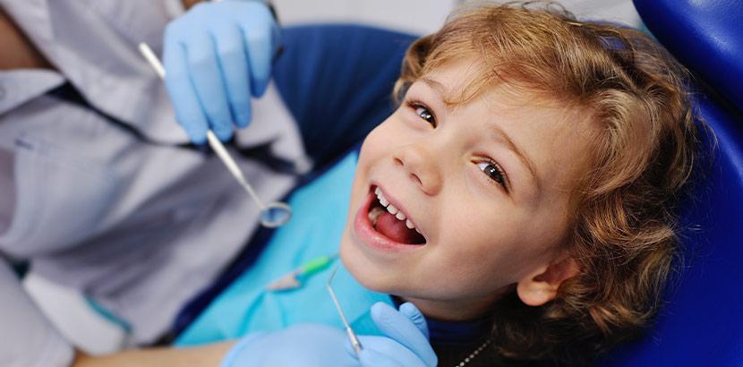 Ein Junge sitzt im Behandlungsstuhl eines Zahnarztes und wartet auf die Behandlung.