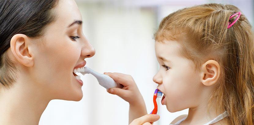 Eine Mutter und ihre Tochter putzen sich gegenseitig die Zähne.