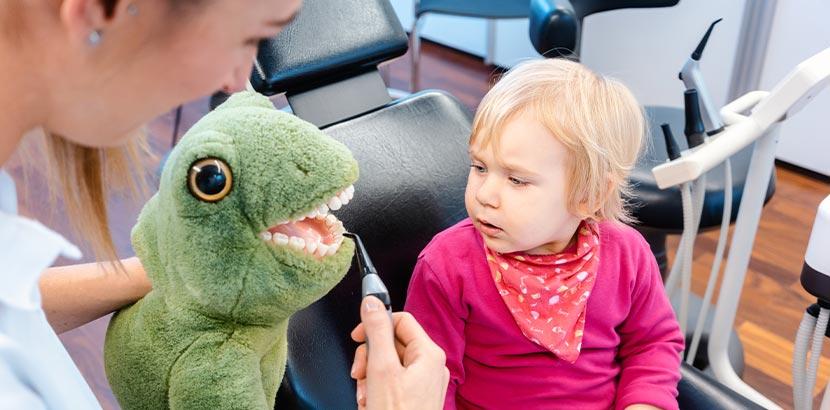 Eine Kinderzahnärztin führt einem Mädchen ihr Werkzeug vor.