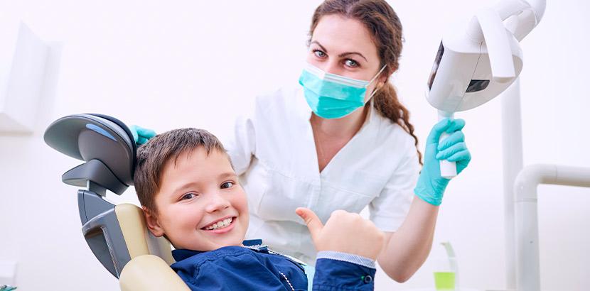Eine Junge zeigt mit seiner Kinderzahnärztin Daumen hoch.