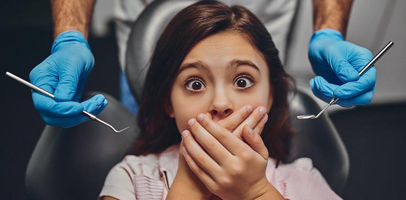 Ein Mädchen hält beim Zahnarzt ihre Hände über den Mund.