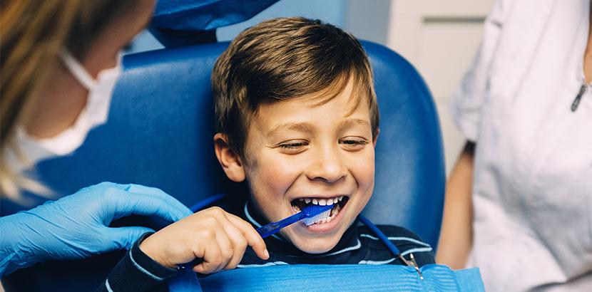 Ein Junge der beim Kinderzahnarzt Zähneputzen lernt.