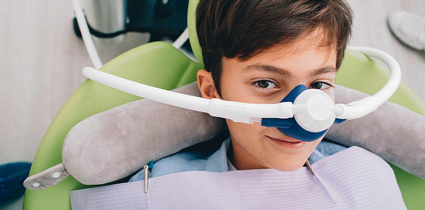 Ein Junge, der beim Zahnarzt über ein Atemgerät mit Lachgas sediert wird.