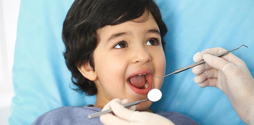 Ein Zahnarzt untersucht den Mund eines Jungen mit Zahnsonde und Mundspiegel.