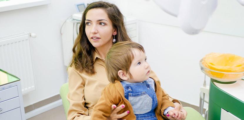 Eine Mutter sitzt mit ihrem Kind auf dem Schoß im Behandlungsraum eines Zahnarztes.