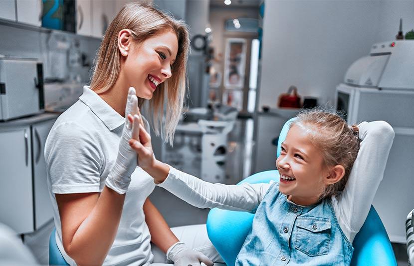 Ein junges Mädchen gibt ihrer Kinderzahnärztin ein High Five.