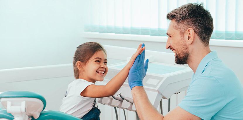 Ein Mädchen gibt ihrem Kinderzahnarzt ein High Five.