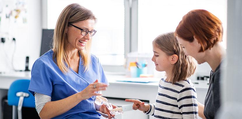 Eine Kinderzahnärztin die eine Mutter und ihre Tochter in der Anamnese berät.
