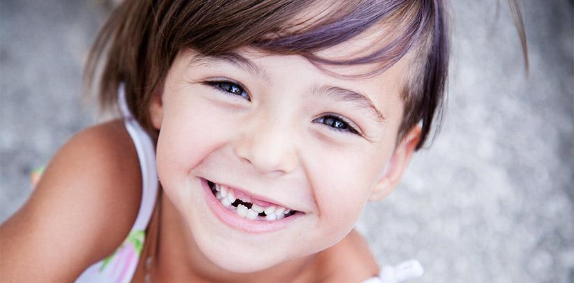 Ein junges Mädchen lächelt mit Zahnlücken im Milchgebiss.