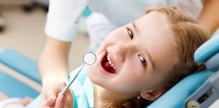 Ein junges Mädchen mit offenem Mund wird mit einem Mundspiegel untersucht.