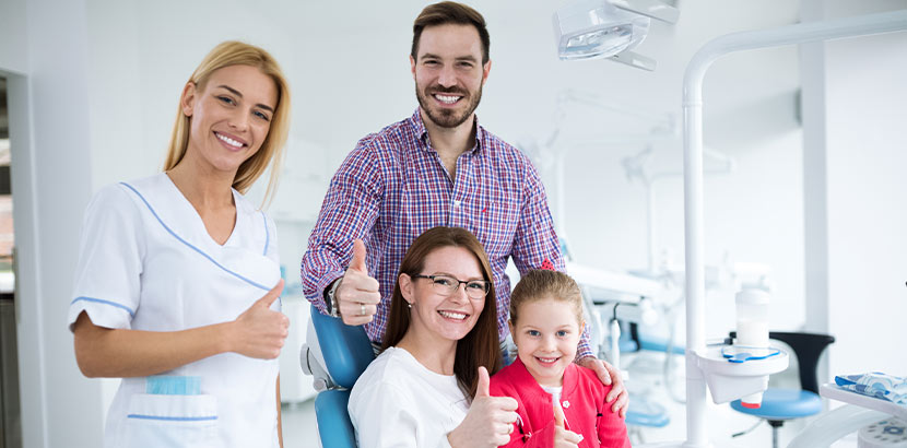Eine Kinderzahnärztin, ihre Patientin und deren Eltern zeigen alle Daumen hoch.