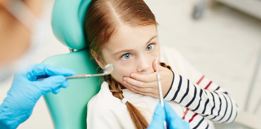 Ein Mädchen legt seine Hand über den Mund und möchte nicht untersucht werden.