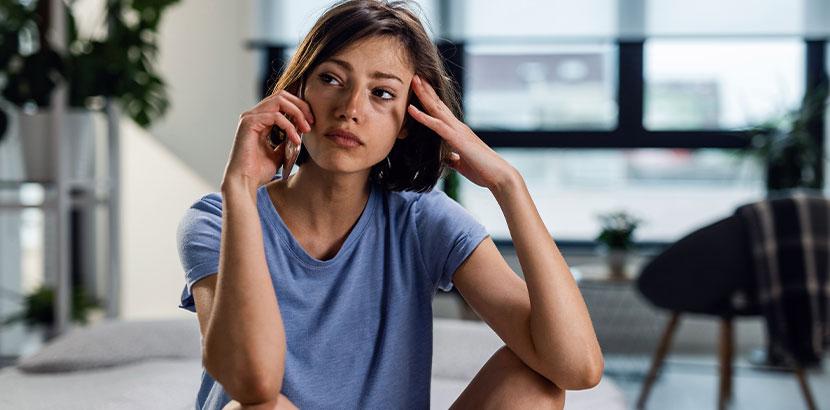 Junge Frau mit verweinten Augen am Telefon, die eine Corona Beratung in Anspruch nimmt.