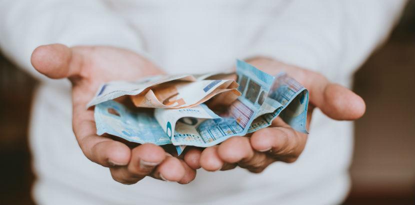 Steuerberatung Salzburg: Hände tragen Geldscheine
