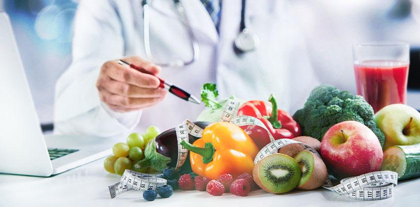 Ein Arzt, auf dessen Schreibtisch gesundes Gemüse wie Paprika, Brokkoli und Kiwi liegen.