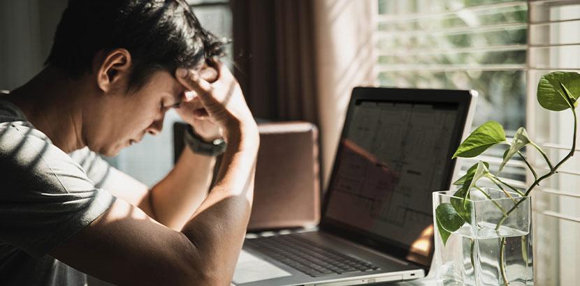 Junger Mann, der verzweifelt vor seinem Laptop sitzt. Online Corona Beratung.