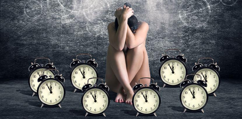 Junge nackte Frau, die zwischen vielen tickenden Uhren sitzt. Pille danach Österreich.