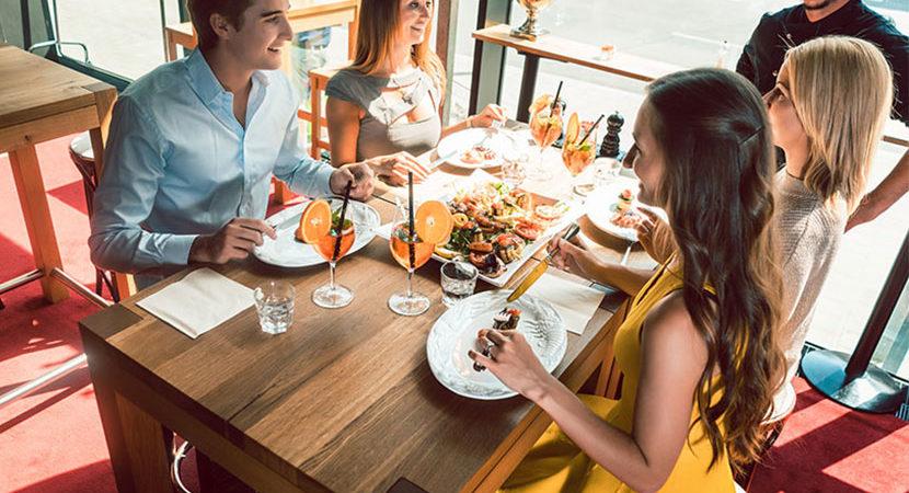 Vier Leute, die beim Essen gehen mit Weißwein anstoßen. Essen gehen Corona Restaurant.