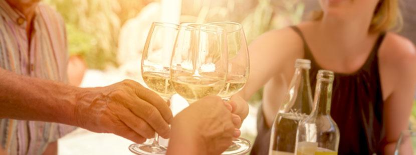 Drei Leute, die beim Essen gehen mit Weißwein anstoßen. Essen gehen Corona Restaurant.