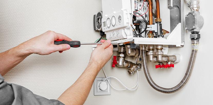 Ein Installateur beim Service einer Gasheizung und Beratung des Kunden.