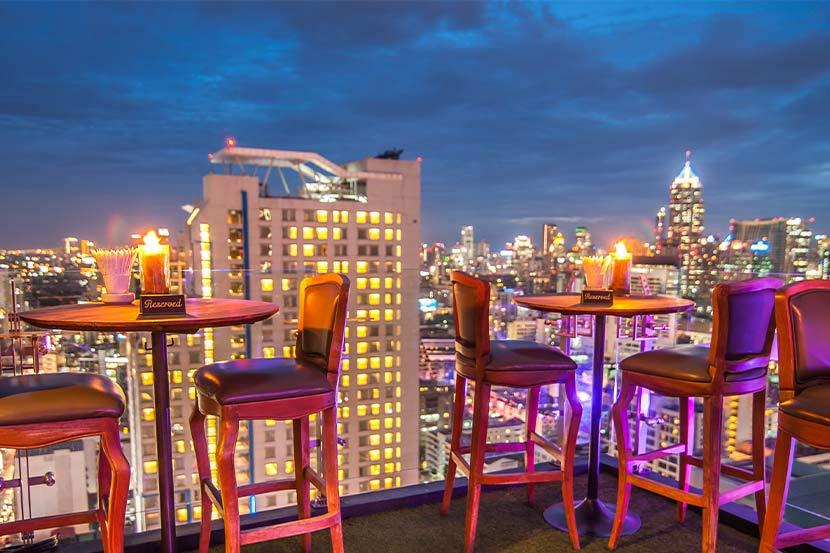 Eine Dachterrasse über den Dächern mit Ausblick auf die Straße. Rooftop Bar Vienna