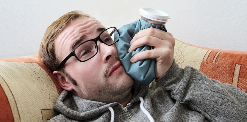 Ein Mann mit Schmerzen im Mund nutzt nach einem Eingriff einen Eisbeutel zur Betäubung.