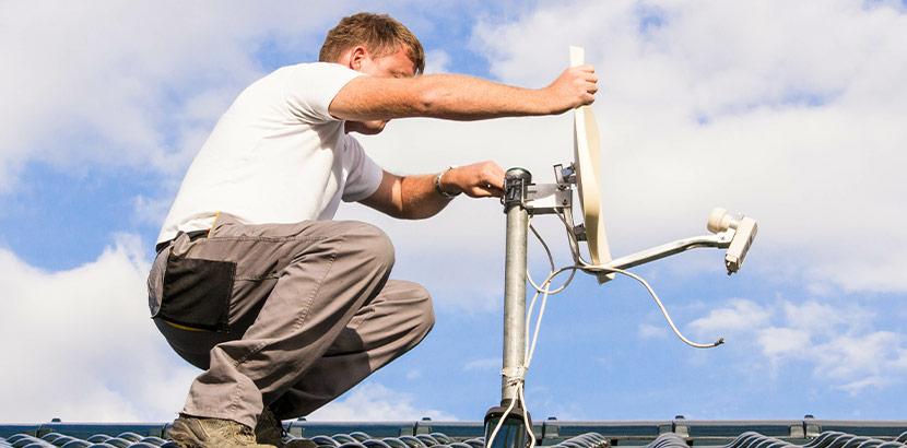 Ein Experte montiert eine Satellitenschüssel als Service auf dem Dach.