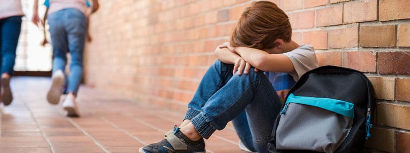 Schuljunge, der in der Schule wegen seiner Dyskalkulie gemobbt wird, und weint.
