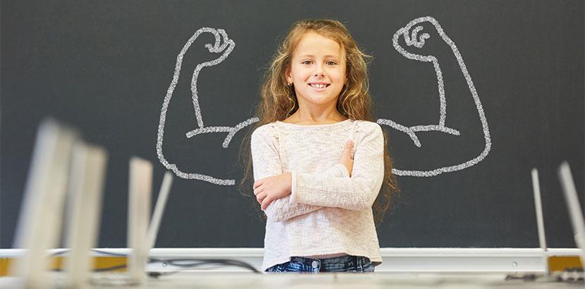 Mädchen vor Schultafel, die wieder Freude am Unterricht hat, da sie Dyskalkulie Förderung bekommt.