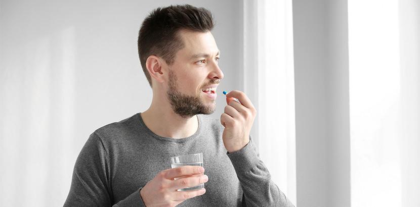 Ein Mann in jungem Alter nimmt eine Pille gegen erektile Störung von seinem Facharzt für Urologie und Andrologie.