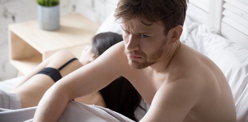 Bild eines Mannes im Bett, der eine unglückliche Beziehung führt.