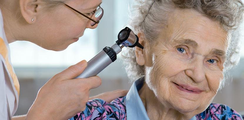 Eine Ärztin verwendet ein Otoskop um den Inhalt des Ohrs zu untersuchen und Daten für die Einstellungen des Hörgeräts zu sammeln.