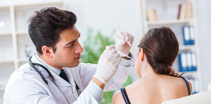 Ein Facharzt untersucht das Innenohr einer Patientin.