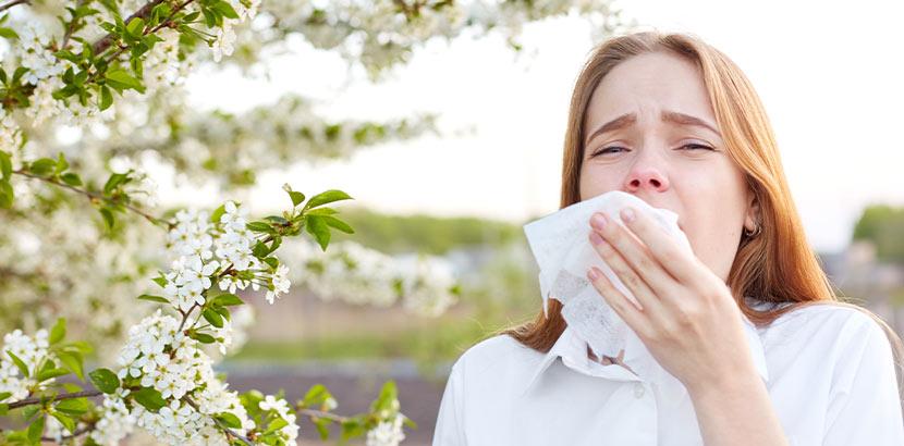 Eine Patientin mit gereizter Nase und Nebenhöhle die ein Taschentuch verwendet.