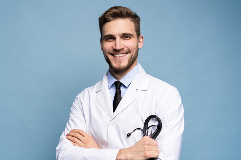 Ein Facharzt für Allgemeinmedizin vor blauem Hintergrund.