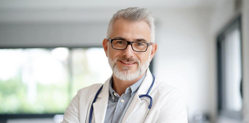 Ein Arzt mit grauem Haar und Brille lächelt.