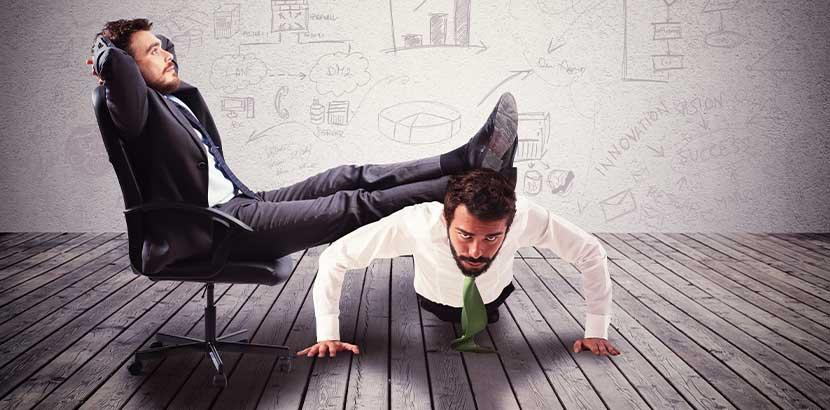 Kollege, der sich auf der Arbeit eines anderen Kollegen ausruht. Mobbing am Arbeitsplatz.