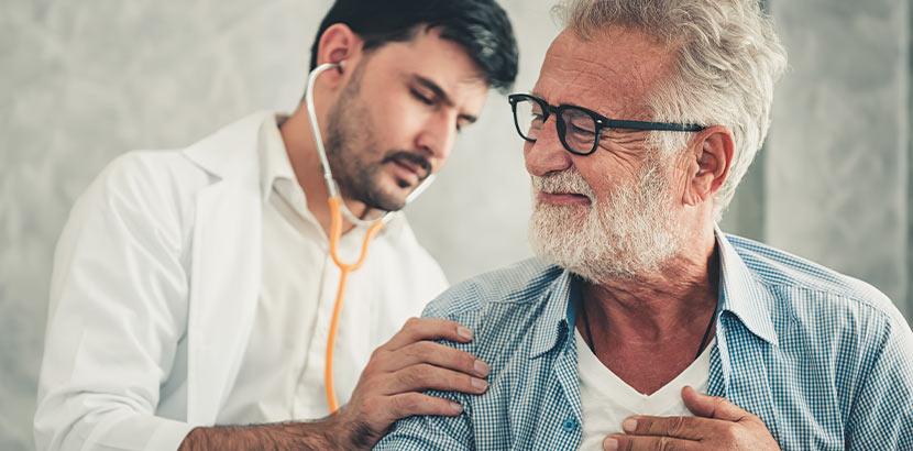 Ein alter Mann der von einem jungen Arzt untersucht wird.