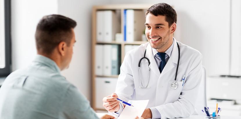 Ein Allgemeinarzt mit guter Bewertung erklärt seinem Patienten die Daten einer Untersuchung.
