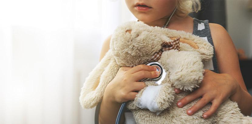 Eine Tochter mit ihrer Mutter und einem Stofftier beim Kinderarzt Termin.