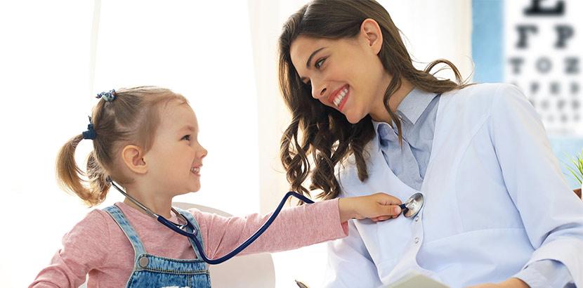 Eine kleine Patientin untersucht ihre Kinderärztin mit dem Stethoskop.