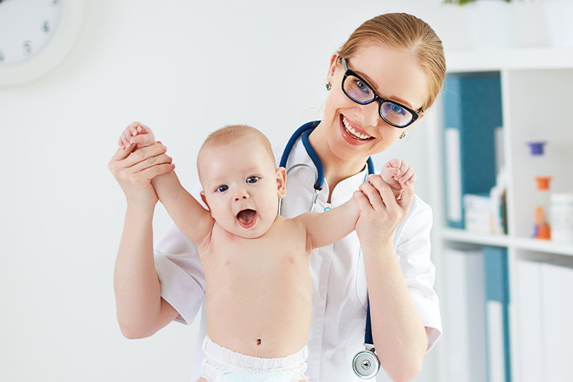 Eine Ärztin mit einem lachenden Baby.