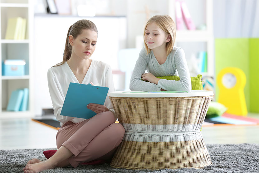 junge Kinderpsychologin ohne Sochen und mit Notizblock spricht mit 9-jährigem Mädchen