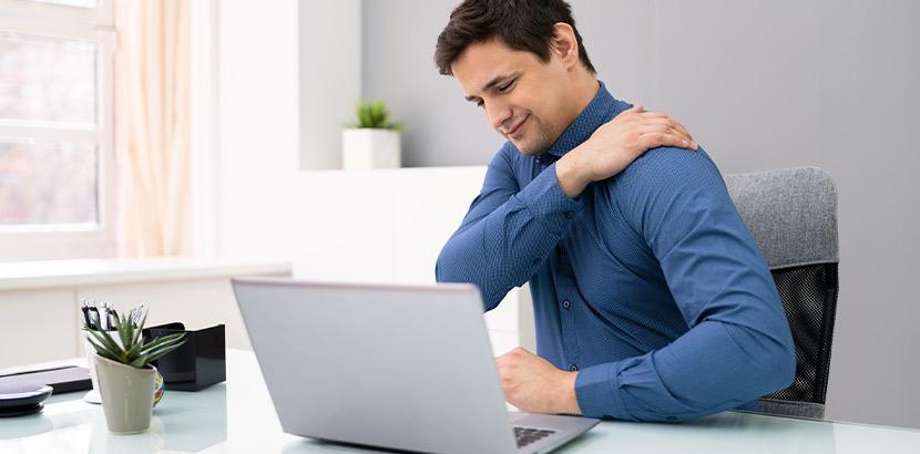 Mann mit Schulterschmerzen und krummer Wirbelsäule legt Hand auf den Rücken.