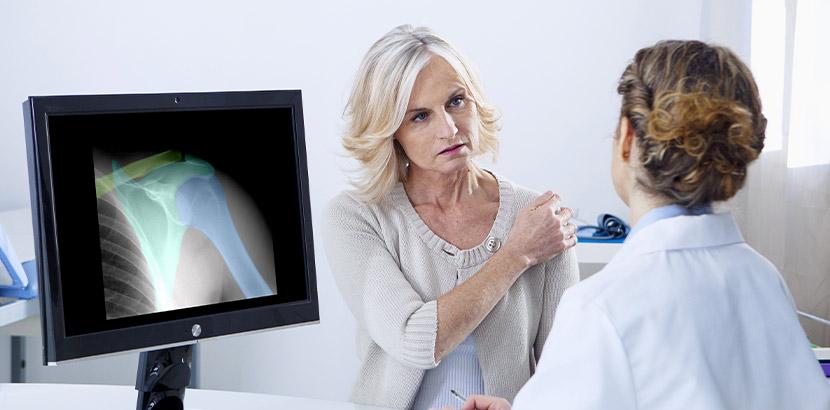 Medizinische Beratung bei der die Orthopädin die Daten eine Schulter-Röntgen bespricht.