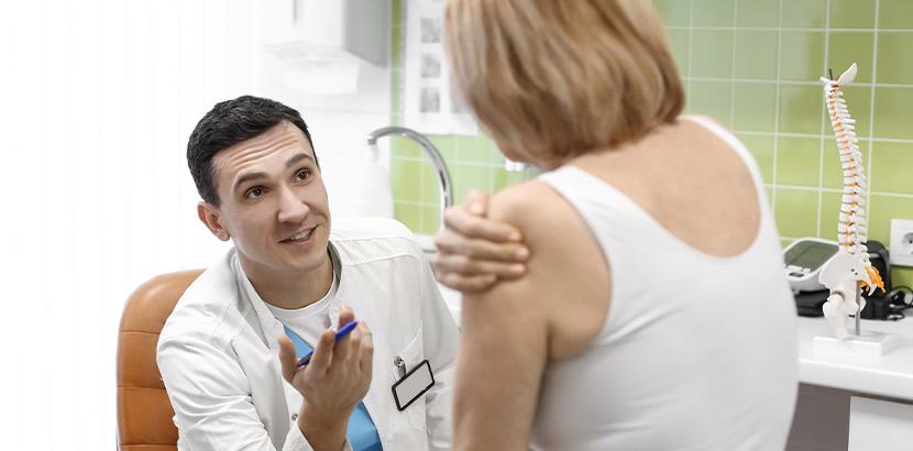 Facharzt mit Ausbildung für Orthopädie und Schulterchirurgie bei Beratung einer Patientin.